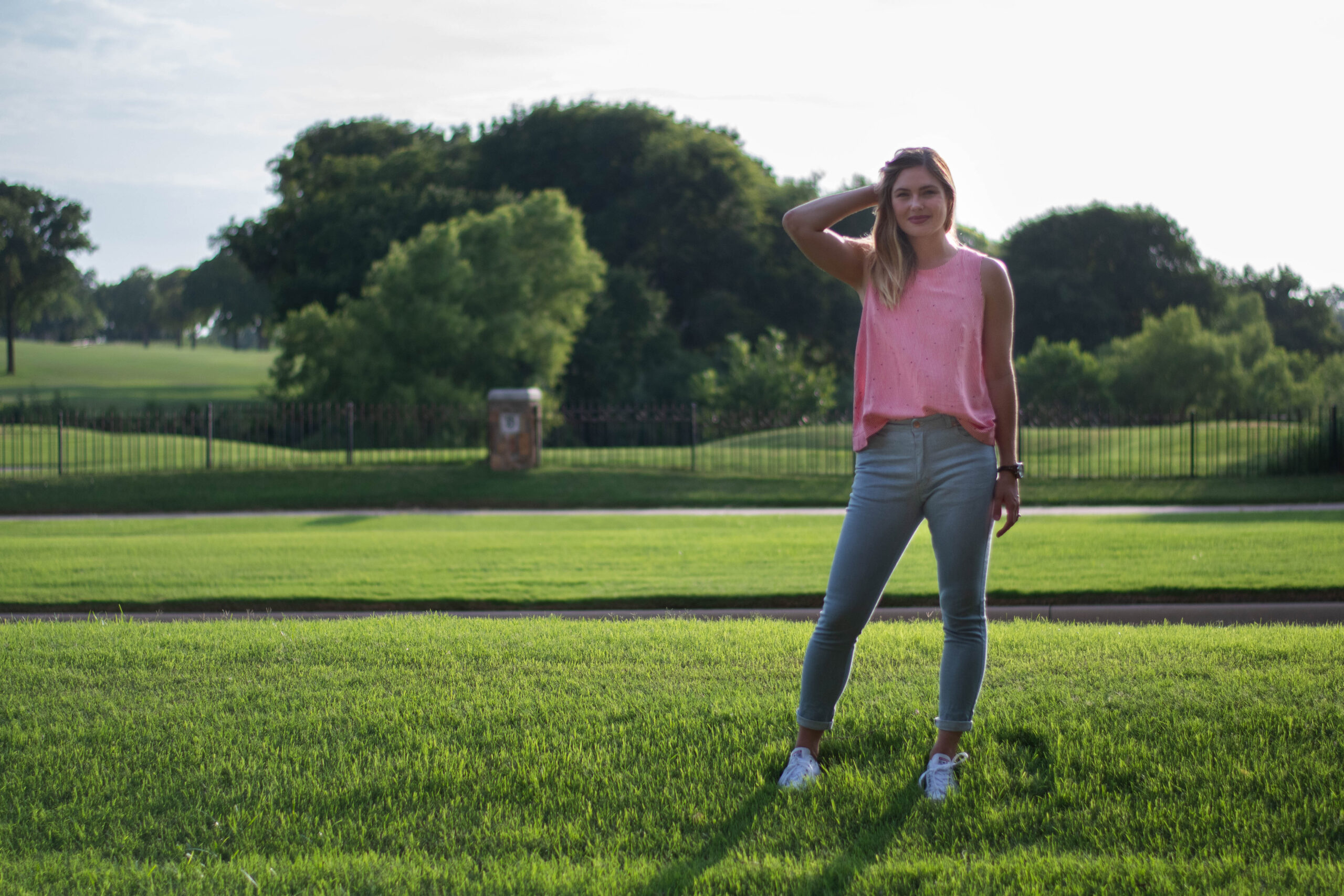 Elizabeth stands on the grass during golden hour wearing a pair of light colored handmade denim jeans, a red and white striped tanktop, and white converse tennishoes. In the background are trees and bushes. Her stance leans slightly to her left, and her right arm is bent upwards, keeping her hair out of her face.