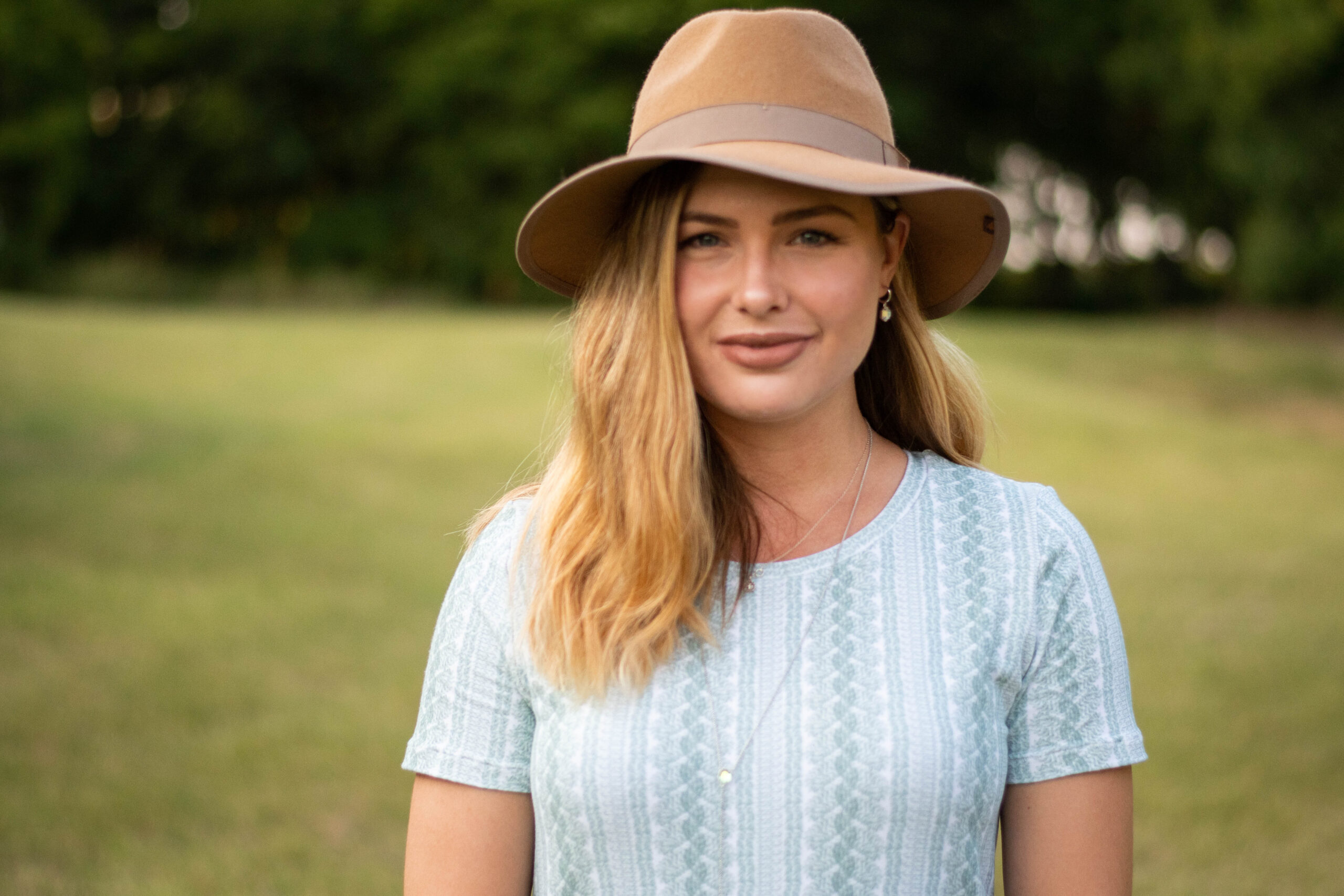 Elizabeth stands in front of a field of grass, wearing a camel colored hat and a t-shirt dress made out of a cable knit sweater look french terry fabric in a sage cream and cream color scheme