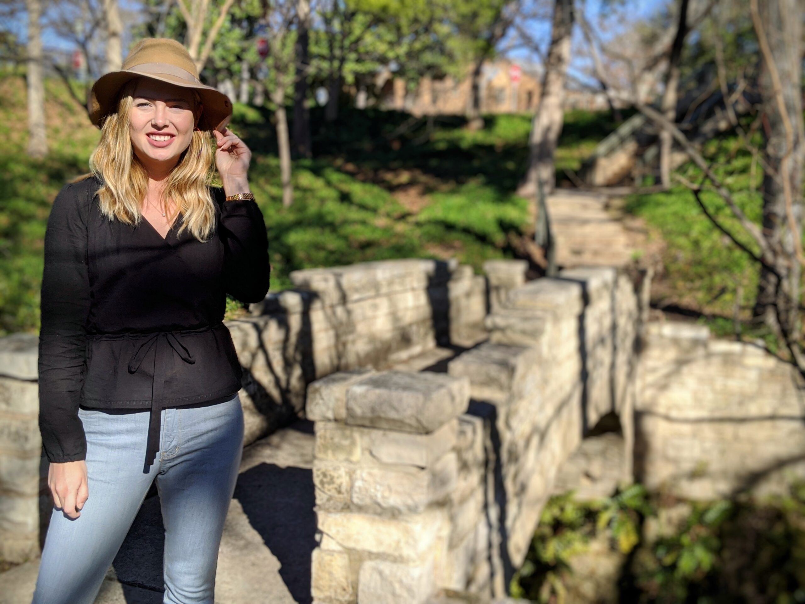 Elizabeth stands near a stone bridge in a park in the wintertime. She is wearing a tan felt hat, and a handmade black wrap top and light colored denim jeans.