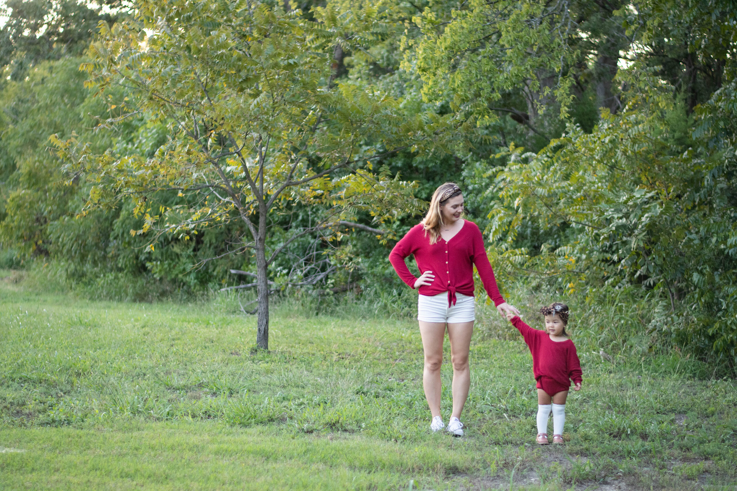 Elizabeth and her daughter stand in a field in front of some green trees with just a hint of autumn coloring on the tips of their leaves. Elizabeth wears a top that she has sewn, and her daughter wears a matching outfit, sewn by Mama, as they hold hands.